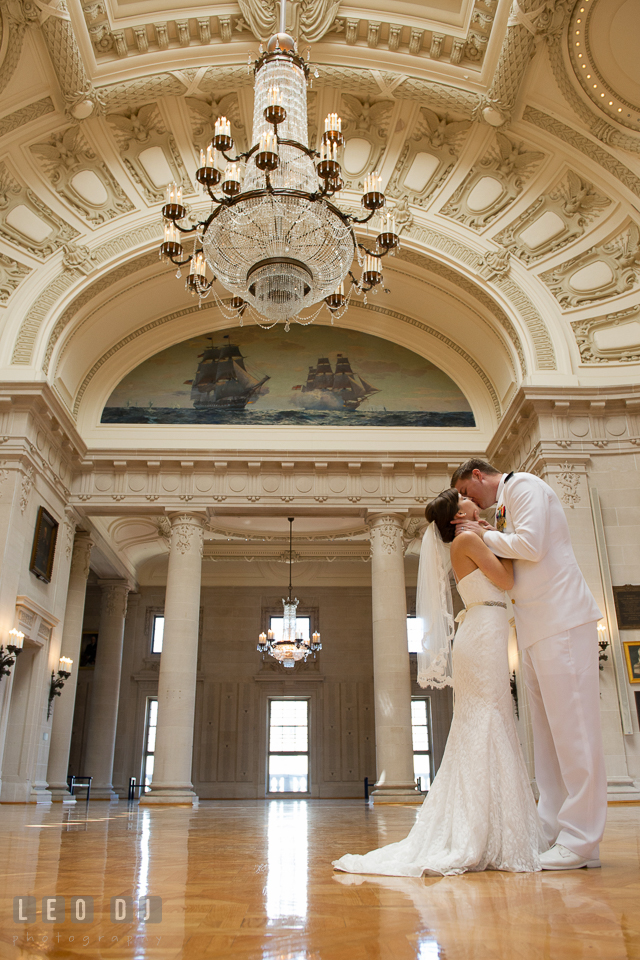 Bride and Groom kissing in the Memorial Hall with the beautiful chandeliers. USNA, US Naval Academy military wedding at Annapolis Maryland, by wedding photographers of Leo Dj Photography. http://leodjphoto.com