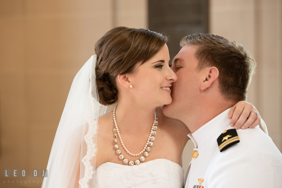 Bride cuddling with Groom whom is kissing her on the cheek. USNA, US Naval Academy military wedding at Annapolis Maryland, by wedding photographers of Leo Dj Photography. http://leodjphoto.com