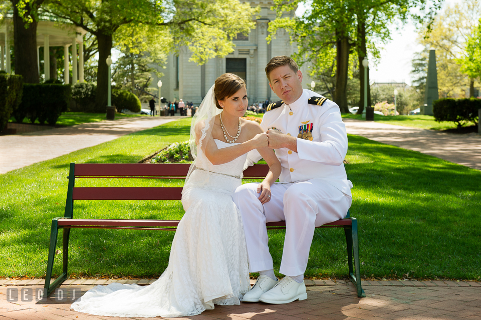 Bride and Groom sitting on the bench in front of the USNA Chapel, pounding their fists. USNA, US Naval Academy military wedding at Annapolis Maryland, by wedding photographers of Leo Dj Photography. http://leodjphoto.com