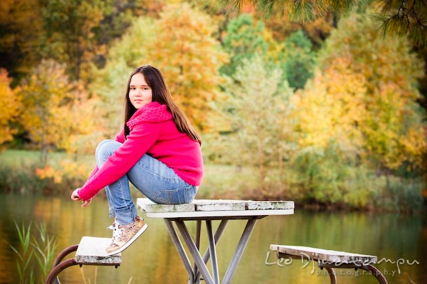 girl in pink sweater and jeans sitting on picnic table, by pond, fall colored trees. Commercial comp card photograper Kent Island Annapolis MD Washington DC