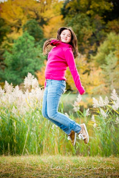 girl in pink sweater and jeans jumping, fall colored trees. Commercial comp card photograper Kent Island Annapolis MD Washington DC