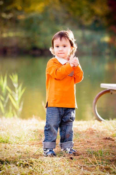 boy in orange shirt and jeans standing by pond. Commercial comp card photograper Kent Island Annapolis MD Washington DC