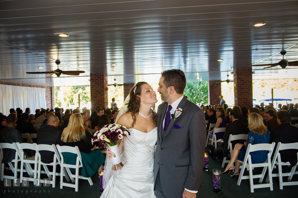 Bride and Groom kissing during the recessional. Harbour View Events Woodbridge Virginia wedding ceremony and reception photo, by wedding photographers of Leo Dj Photography. http://leodjphoto.com