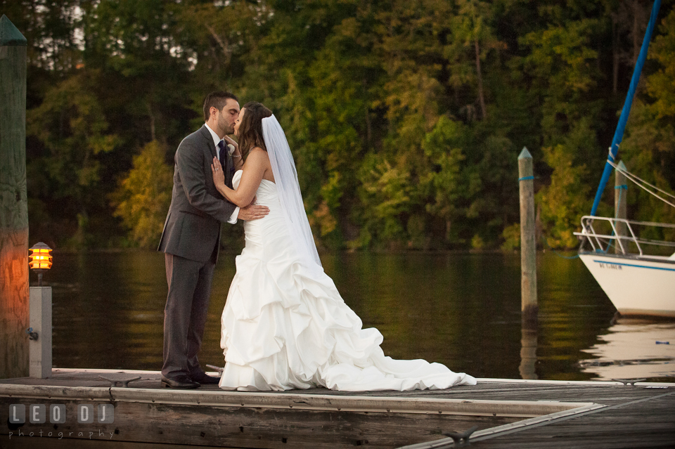Groom kissing Bride by the dock. Harbour View Events Woodbridge Virginia wedding ceremony and reception photo, by wedding photographers of Leo Dj Photography. http://leodjphoto.com