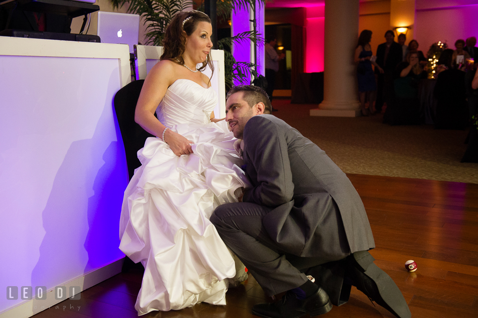 Groom trying to find Bride's garter. Harbour View Events Woodbridge Virginia wedding ceremony and reception photo, by wedding photographers of Leo Dj Photography. http://leodjphoto.com