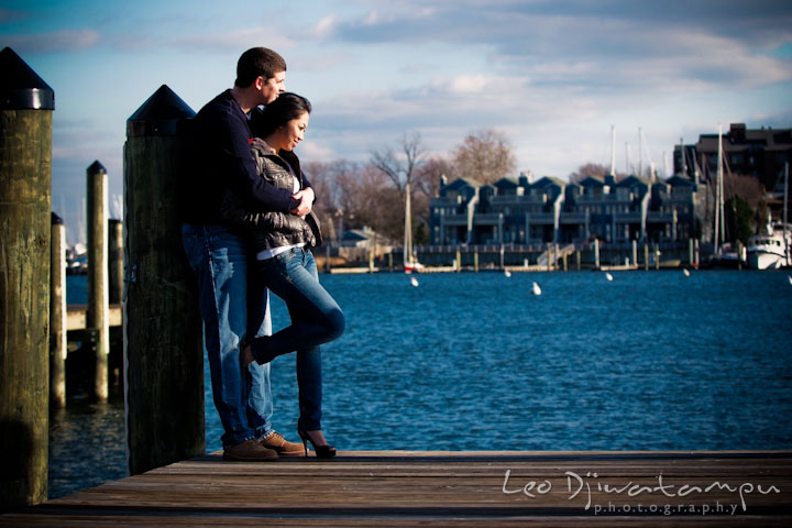 Fiancé and his fiancée hugging and leaning on boat pier pole. City or urban setting pre-wedding or engagement photo session at Annapolis, by Annapolis wedding photographer, Leo Dj Photography.