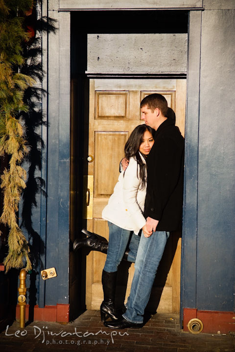 Engaged girl leaning on her fiancé by a wooden door. City or urban setting pre-wedding or engagement photo session at Annapolis, by Annapolis wedding photographer, Leo Dj Photography.