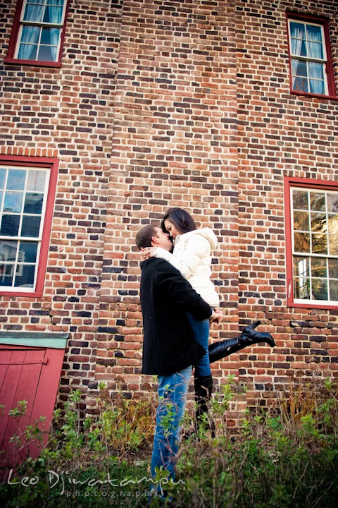 Engaged guy lifted up his fiancée by a historic brick house. City or urban setting pre-wedding or engagement photo session at Annapolis, by Annapolis wedding photographer, Leo Dj Photography.