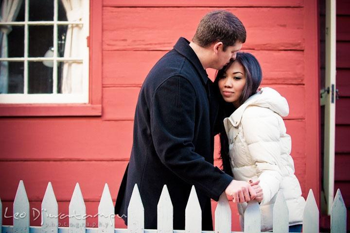 Engaged guy kissing his fiancée behind a white picket fence, by a red house. City or urban setting pre-wedding or engagement photo session at Annapolis, by Annapolis wedding photographer, Leo Dj Photography.
