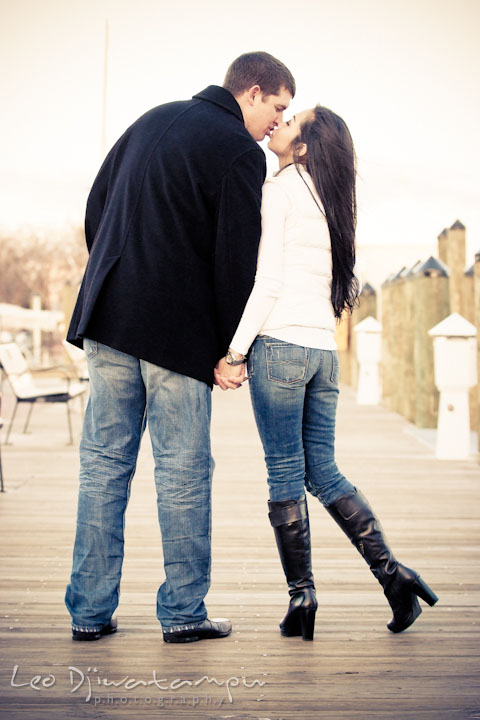 Engaged couple stopped walking on the pier and kissed. City or urban setting pre-wedding or engagement photo session at Annapolis, by Annapolis wedding photographer, Leo Dj Photography.