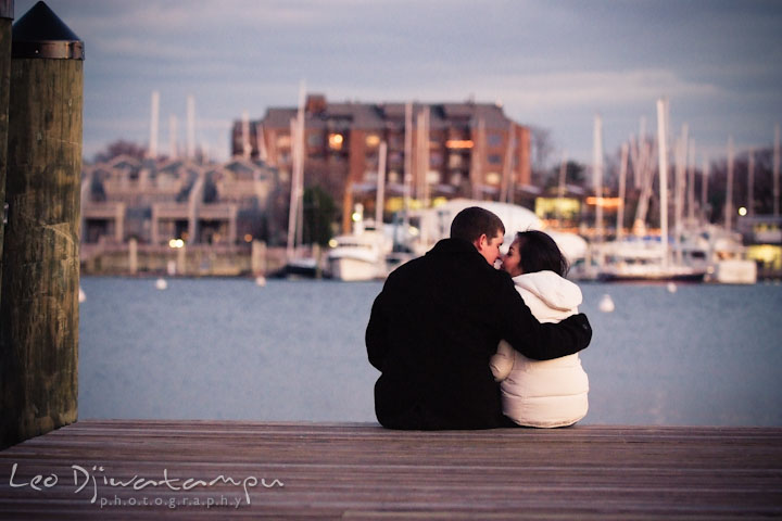 Engaged couple sitting at the edge of a boat pier, by the water. City or urban setting pre-wedding or engagement photo session at Annapolis, by Annapolis wedding photographer, Leo Dj Photography.