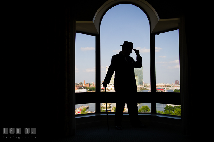 Silhouette of Groom in his tuxedo with tophat and cane. Baltimore Maryland Science Center wedding, getting ready photo at Royal Sonesta Harbor Court hotel, by wedding photographers of Leo Dj Photography. http://leodjphoto.com