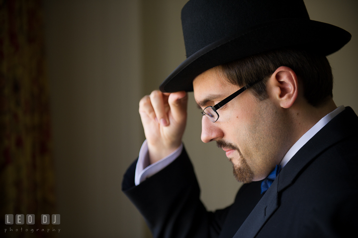 Groom holding his tophat. Baltimore Maryland Science Center wedding, getting ready photo at Royal Sonesta Harbor Court hotel, by wedding photographers of Leo Dj Photography. http://leodjphoto.com
