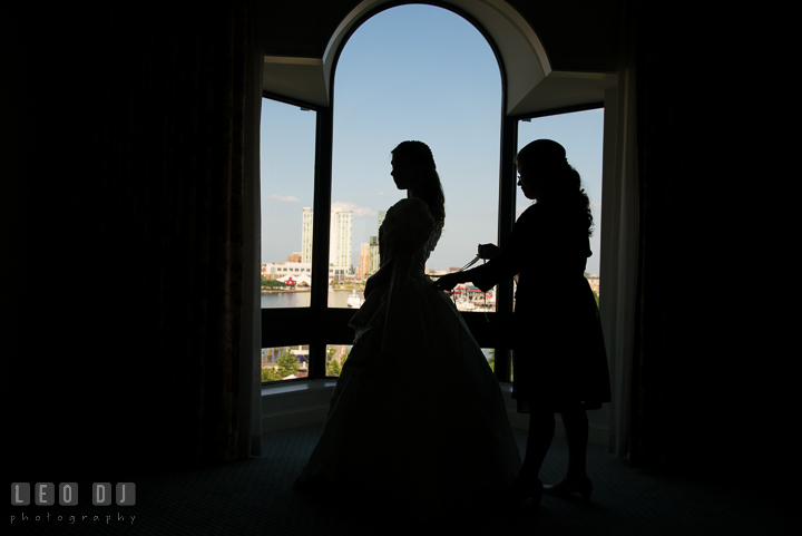 Maid of Honor lacing up Bride's wedding gown. Baltimore Maryland Science Center wedding, getting ready photo at Royal Sonesta Harbor Court hotel, by wedding photographers of Leo Dj Photography. http://leodjphoto.com