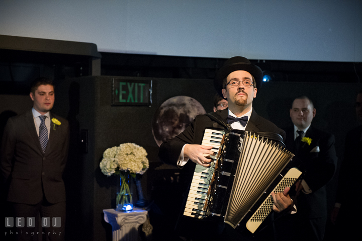 Groom playing accordion during the ceremony. Baltimore Maryland Science Center wedding reception and ceremony photo, by wedding photographers of Leo Dj Photography. http://leodjphoto.com