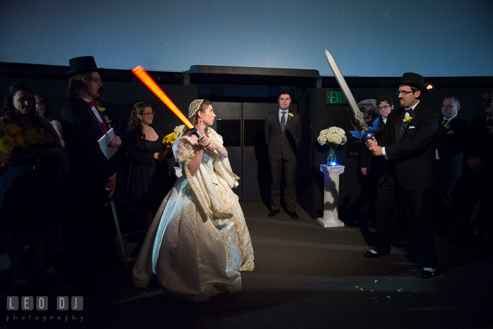 Groom had to battle with Bride's evil twin who was using a red light saber. Baltimore Maryland Science Center wedding reception and ceremony photo, by wedding photographers of Leo Dj Photography. http://leodjphoto.com