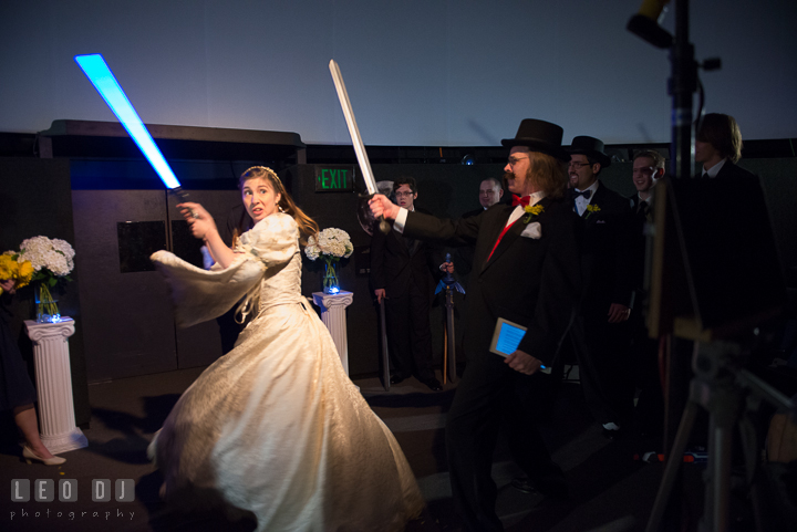 Bride battled the evil lord using a blue light saber. Baltimore Maryland Science Center wedding reception and ceremony photo, by wedding photographers of Leo Dj Photography. http://leodjphoto.com