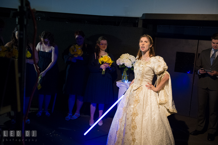 Bride holding a blue light saber told the evil lord to go away. Baltimore Maryland Science Center wedding reception and ceremony photo, by wedding photographers of Leo Dj Photography. http://leodjphoto.com