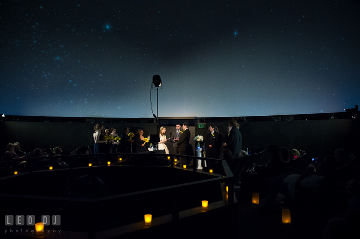 Wedding ceremony in the planetarium with candle lights with starry night backdrop in the planetarium sky. Baltimore Maryland Science Center wedding reception and ceremony photo, by wedding photographers of Leo Dj Photography. http://leodjphoto.com