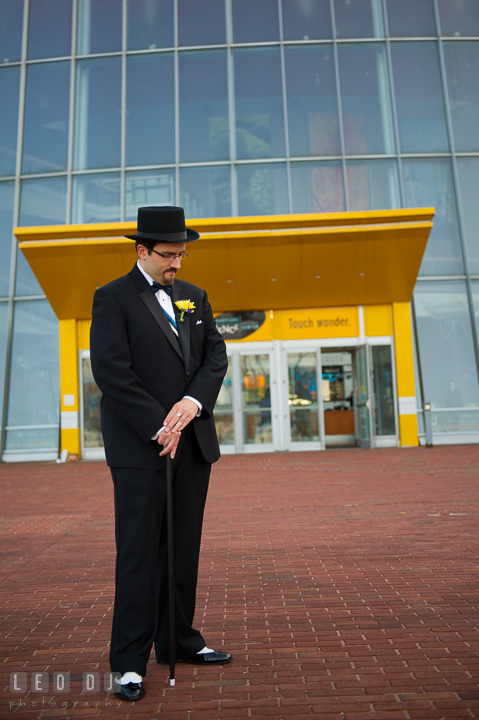 Full body shot of Groom and his traditional Estonian formal outfit with his tophat and cane. Baltimore Maryland Science Center wedding reception and ceremony photo, by wedding photographers of Leo Dj Photography. http://leodjphoto.com