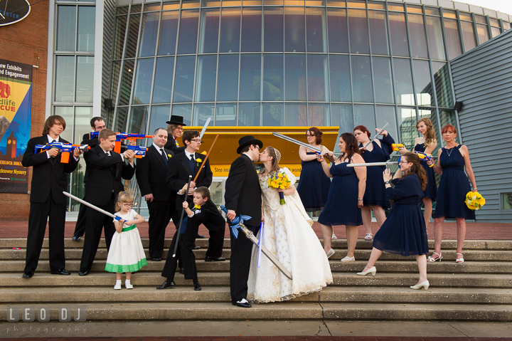 Bride and Groom kissing, while Best Man, Maid of Honor, Groomsmen, Bridesmaids, Flower Girl, and Ring Bearer pretending to be at war against each other.. Baltimore Maryland Science Center wedding reception and ceremony photo, by wedding photographers of Leo Dj Photography. http://leodjphoto.com