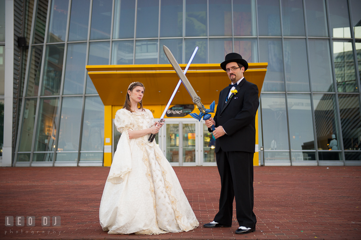 Bride and Groom posing with light saber and Zelda's sword. Baltimore Maryland Science Center wedding reception and ceremony photo, by wedding photographers of Leo Dj Photography. http://leodjphoto.com