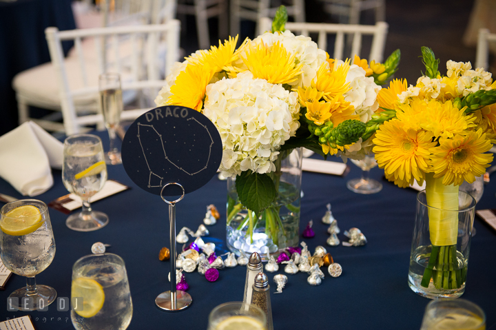 White and yellow floral table centerpiece and Draco star constellation table name. Baltimore Maryland Science Center wedding reception and ceremony photo, by wedding photographers of Leo Dj Photography. http://leodjphoto.com