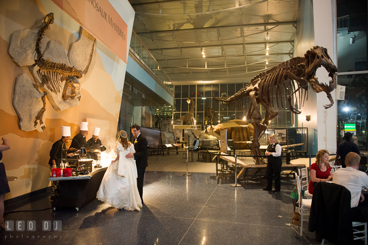 Bride and Groom getting their dinner from one of the food stations with Dinosaur fossil bones in the background. Baltimore Maryland Science Center wedding reception and ceremony photo, by wedding photographers of Leo Dj Photography. http://leodjphoto.com