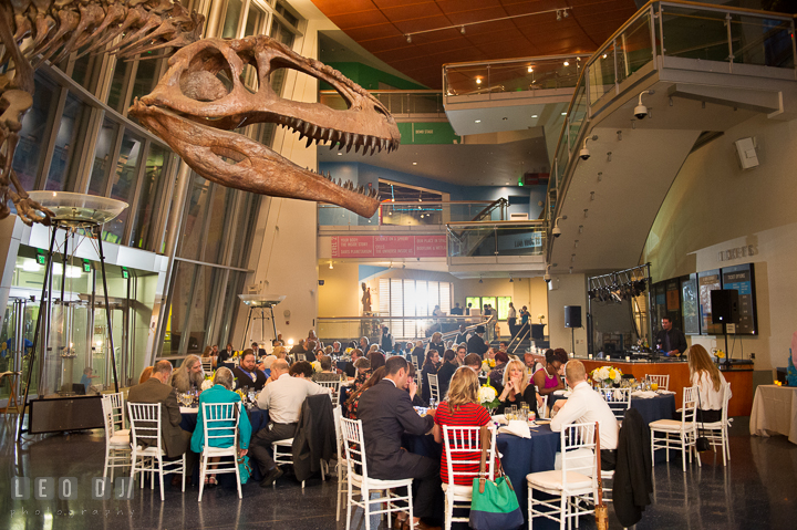 View of guests eating at their tables in the main hall with a T-Rex bones and skull in the foreground. Baltimore Maryland Science Center wedding reception and ceremony photo, by wedding photographers of Leo Dj Photography. http://leodjphoto.com