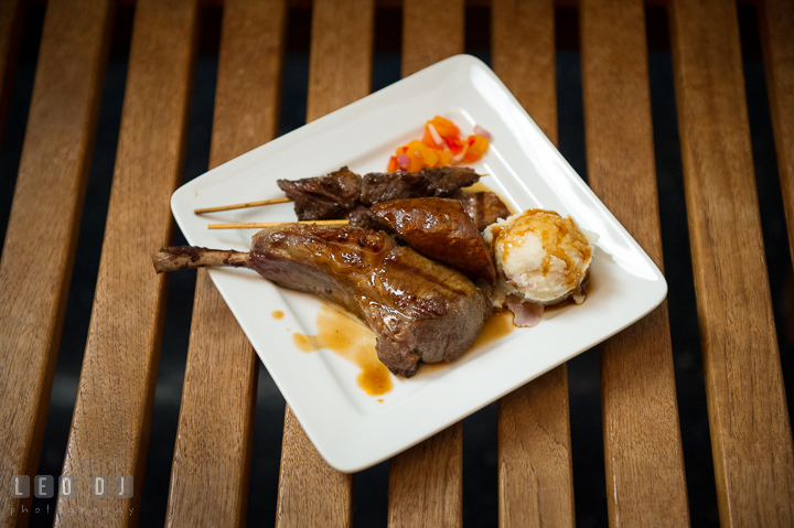 A plate with grilled selection including sausage, veal rib, and skewered beef from Aramark catering