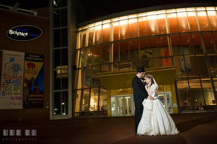 Bride and Groom cuddling with the building in the Background. Baltimore Maryland Science Center wedding reception and ceremony photo, by wedding photographers of Leo Dj Photography. http://leodjphoto.com
