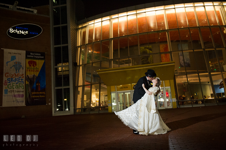 Bride and Groom doing the dip kissing with the beautiful Maryland Science Center building the background. Baltimore Maryland Science Center wedding reception and ceremony photo, by wedding photographers of Leo Dj Photography. http://leodjphoto.com