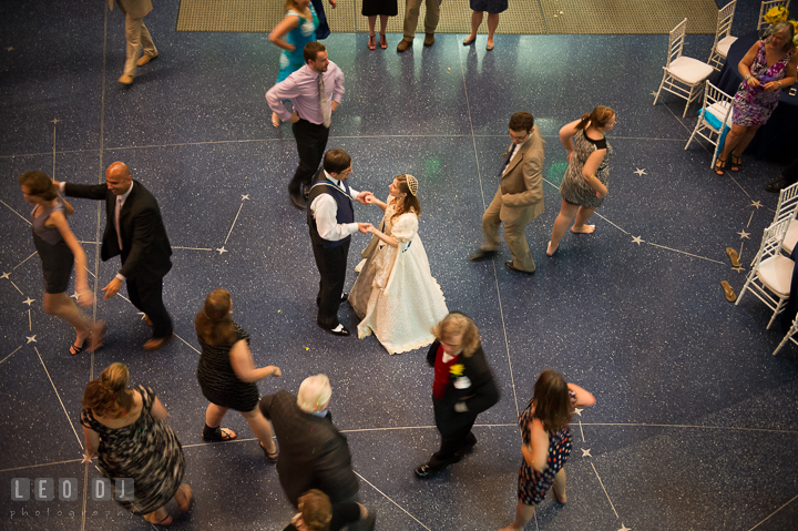 Guests twirling and dancing Estonian traditional folk dance around Bride and Groom. Baltimore Maryland Science Center wedding reception and ceremony photo, by wedding photographers of Leo Dj Photography. http://leodjphoto.com
