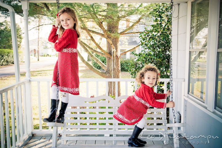 two girls playing on swing on porch. Candid children photographer St Michael Tilghman Island MD