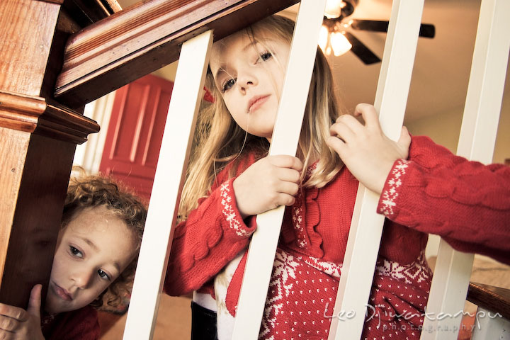 two sisters posing by stair railings. Candid children photographer St Michael Tilghman Island MD