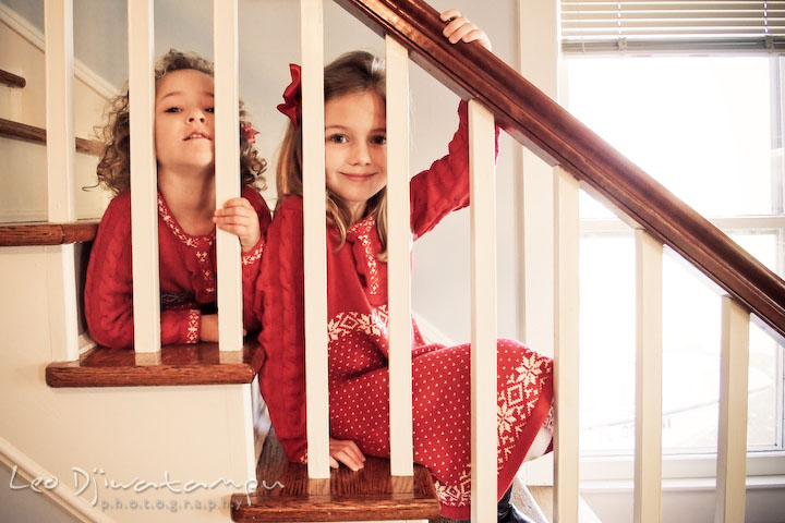 two sisters, posing behind stair railing, smiling. Candid children photographer St Michael Tilghman Island MD