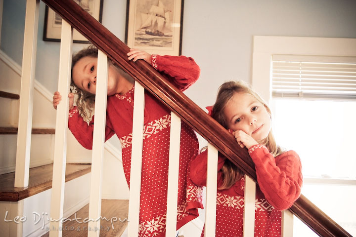 two cute girls posing on stair railings. Candid children photographer St Michael Tilghman Island MD