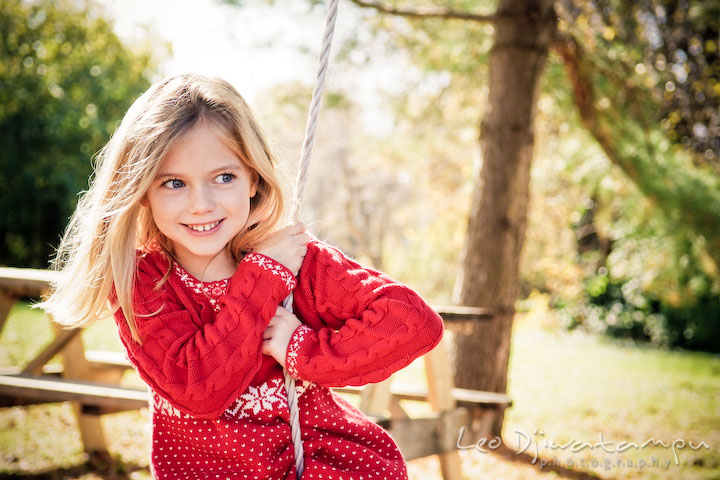 cute girl with blonde hair and blue eyes, playing swing. Candid children photographer St Michael Tilghman Island MD