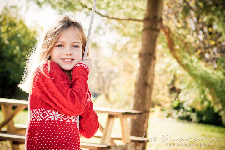 blond girl in red dress playing swing, smiling. Candid children photographer St Michael Tilghman Island MD