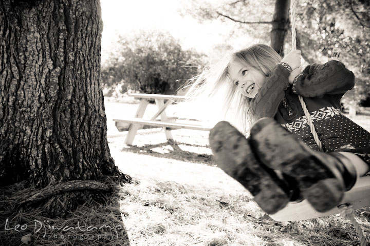 girl swinging under a tree in black and white. Candid children photographer St Michael Tilghman Island MD