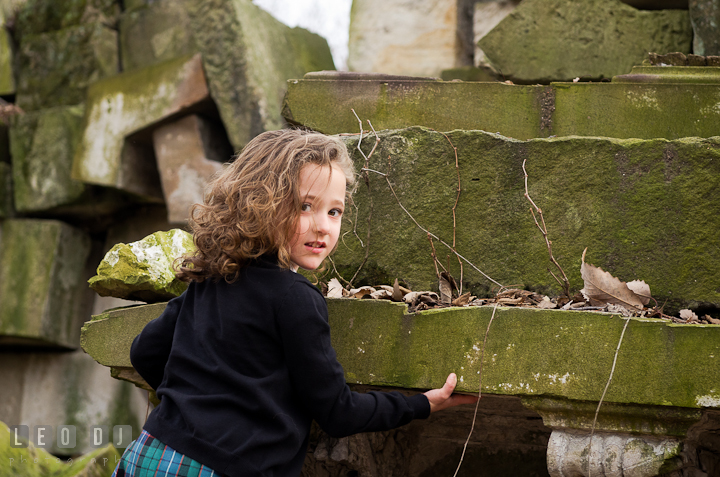 Girl climbing up wall ruins. Washington DC fun and candid children lifestyle photo session of Helena and Vivian by photographers of Leo Dj Photography.