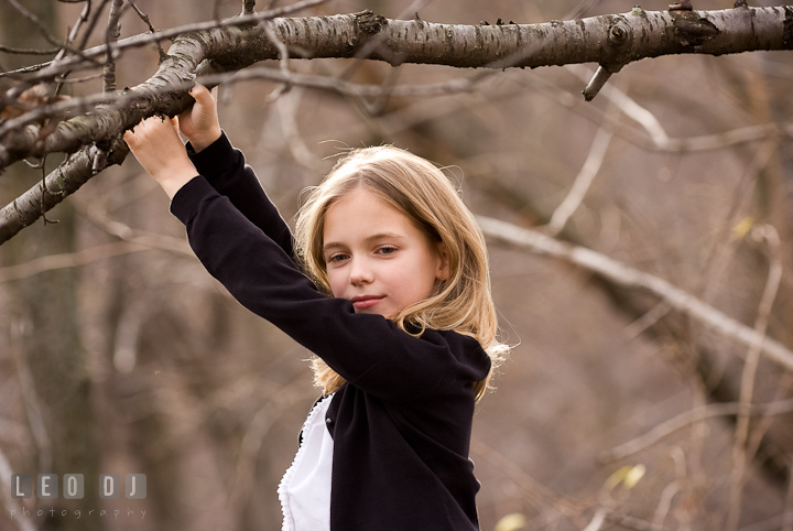 Girl hanging by a tree branch. Washington DC fun and candid children lifestyle photo session of Helena and Vivian by photographers of Leo Dj Photography.