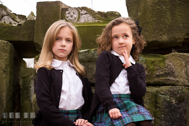 Two sisters posing by stone ruins. Washington DC fun and candid children lifestyle photo session of Helena and Vivian by photographers of Leo Dj Photography.