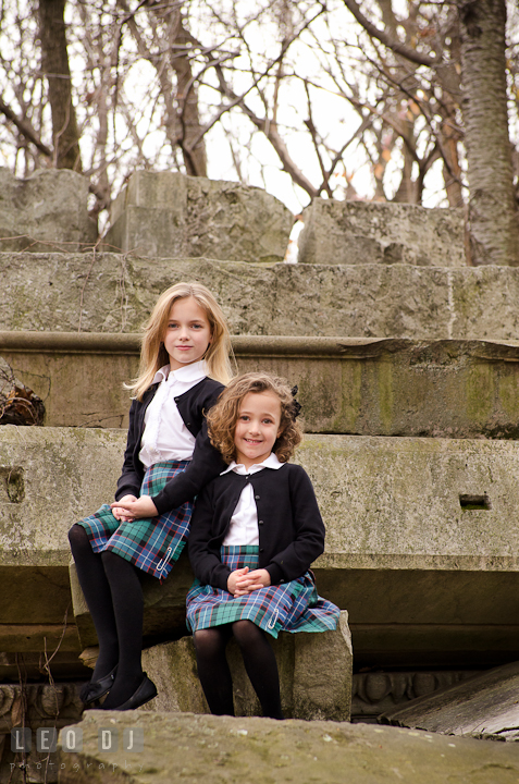 Two sisters sitting on building stone ruins. Washington DC fun and candid children lifestyle photo session of Helena and Vivian by photographers of Leo Dj Photography.