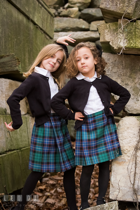 Two sisters, one blonde, one curly brunette, posing by stone ruins. Washington DC fun and candid children lifestyle photo session of Helena and Vivian by photographers of Leo Dj Photography.