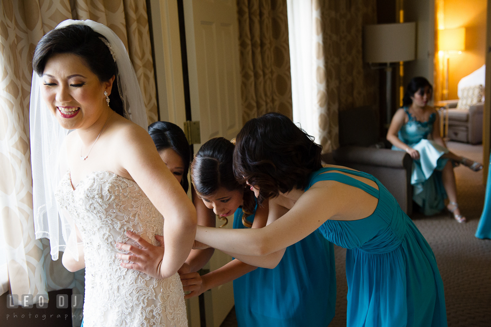 Sheraton Hotel Reston Virginia Bridesmaid helping Bride put on wedding gown photo by Leo Dj Photography