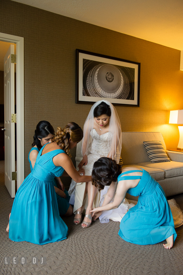 Sheraton Hotel Reston Virginia Bridesmaid helping Bride put on shoes photo by Leo Dj Photography