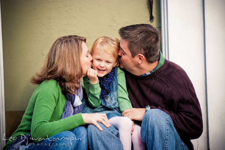 Mom and dad kissing daughter. Annapolis Maryland candid lifestyle family portrait photography