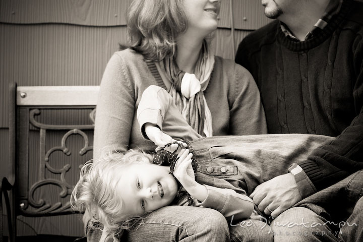 Little girl laying on mom and dad's lap. Annapolis Maryland candid lifestyle family portrait photography