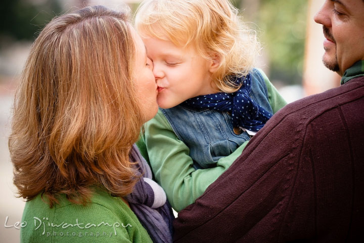 Mom kissed her little daughter. Dad smiling. Annapolis Maryland candid lifestyle family portrait photography